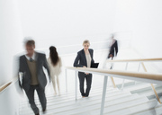 Business people rushing along stairs - CAIF00252