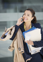 Smiling businesswoman talking on cell phone and carrying paperwork - CAIF00270