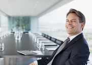 Portrait of smiling businessman in conference room - CAIF00291