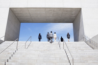 Business people ascending concrete steps toward blue sky - CAIF00297