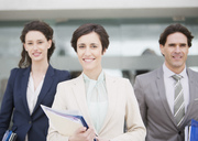 Portrait of smiling business people holding files - CAIF00306