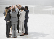 Business people standing in huddle with arms raised - CAIF00312