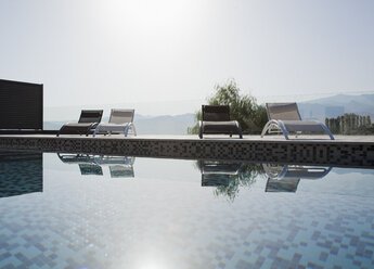 Sun shining over lounge chairs and swimming pool - CAIF00390