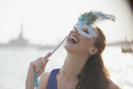 Laughing woman with mask at waterfront in Venice - CAIF00493