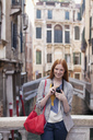 Portrait of smiling woman with camera in Venice - CAIF00514