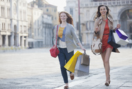 Happy friends with shopping bags running in St. Mark's Square in Venice - CAIF00526