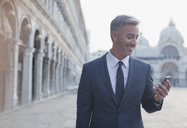 Smiling businessman checking cell phone in St. Mark's Square in Venice - CAIF00550