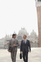 Smiling businessmen walking through St. Mark's Square in Venice - CAIF00562