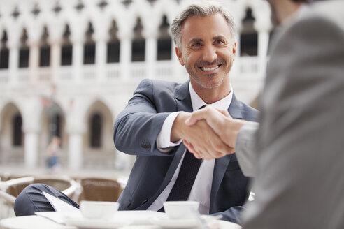 Smiling businessmen shaking hands at sidewalk cafe - CAIF00568