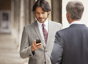 Businessman checking cell phone - CAIF00583