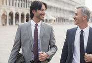 Smiling businessmen talking in St. Mark's Square in Venice - CAIF00592