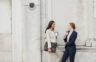 Smiling businesswomen drinking coffee and talking against building wall - CAIF00595