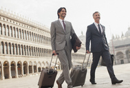 Smiling businessmen walking with suitcases through St. Mark's Square in Venice - CAIF00616
