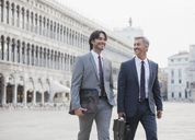 Smiling businessmen walking across St. Mark's Square in Venice - CAIF00625