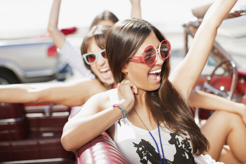 Women cheering in convertible - CAIF00694