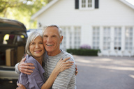 Smiling older couple hugging outdoors - CAIF00715