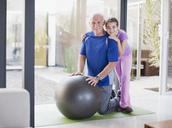 Girl hugging grandfather on exercise ball - CAIF00727