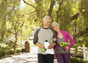 Older couple walking together outdoors - CAIF00730