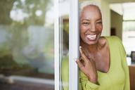 Older woman smiling in doorway - CAIF00736