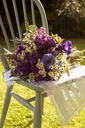 Bouquet of flowers in chair outdoors - CAIF00748