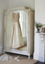Wedding gown hanging from wardrobe - CAIF00766