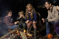 Family eating around campfire at night - CAIF00847