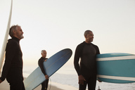 Older surfers carrying boards on beach - CAIF00862