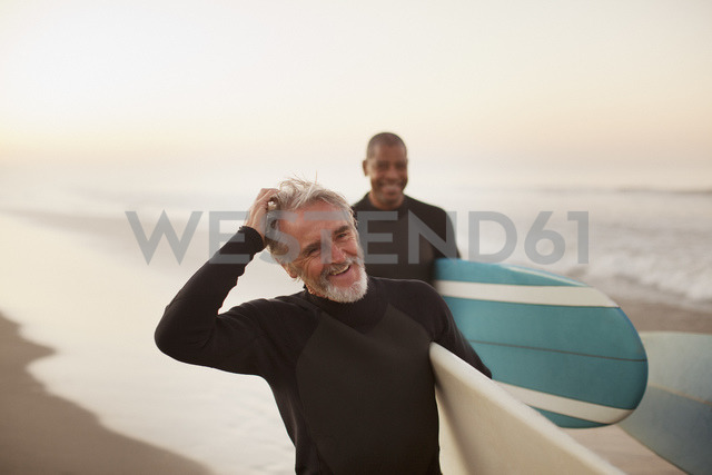 Older surfers carrying boards on beach - CAIF00865