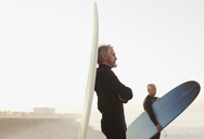 Older surfer leaning on board on beach - CAIF00871