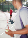 Older men playing tennis on court - CAIF00886