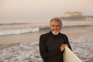 Older surfer carrying board on beach - CAIF00889