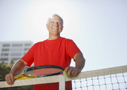 Older man playing tennis on court - CAIF00892