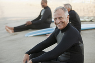 Older surfers sitting on boards on beach - CAIF00895