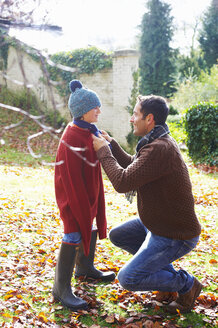 Father tying son's scarf outdoors - CAIF00901