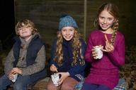 Smiling children eating french fries at night - CAIF00916