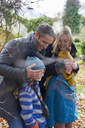 Parents covering children's eyes outdoors - CAIF00922