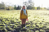 Smiling girl standing in muddy field - CAIF00928