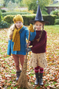 Girls playing with witch's hat and broom outdoors - CAIF00937