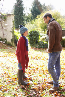 Father and son walking in autumn leaves - CAIF00946