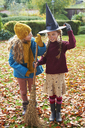 Girls playing with witch's hat and broom outdoors - CAIF00955