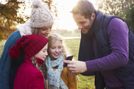 Family using cell phone together outdoors - CAIF00967