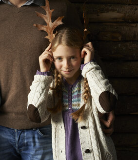 Girl using leaves as antlers - CAIF00970