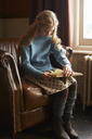 Girl reading book in armchair - CAIF00976