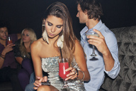 Woman with cocktail checking cell phone in nightclub - CAIF01057
