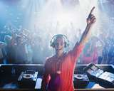 Portrait of enthusiastic DJ with arm raised and people on dance floor in background - CAIF01063