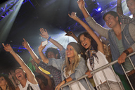 Enthusiastic crowd with arms raised behind railing at concert - CAIF01084