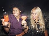Portrait of enthusiastic couple toasting cocktails in nightclub - CAIF01087