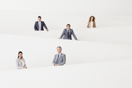 Portrait of smiling business people staggered on modern staircase - CAIF01129