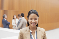 Portrait of smiling businesswoman with co-workers meeting in background - CAIF01135