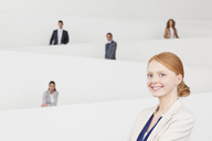 Portrait of smiling businesswoman with co-workers on staircase in background - CAIF01138